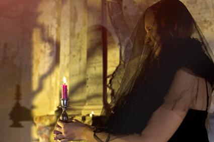 Woman with candle standing by an ancient altar