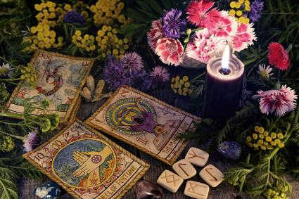 Still life with old tarot cards, purple candle, runes and flowers