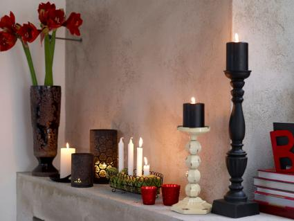 Various candles and vase on fireplace
