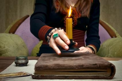 Witch holds a golden candle