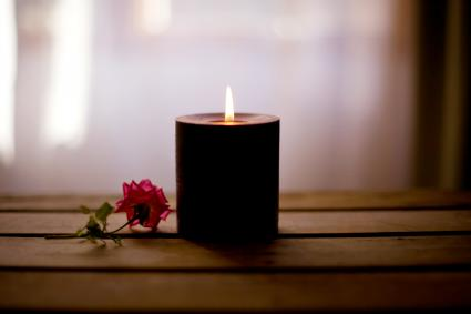Single black candle burning with a pink tea rose flower