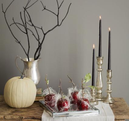 Candied apples, candles, a pumpkin and decorations for Halloween