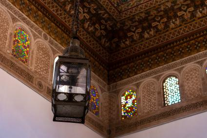 Moroccan lantern hanging from a decorated ceiling
