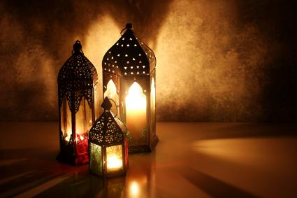 Ornamental Arabic lanterns with burning candles on table
