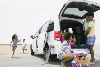 Family unloading van at beach