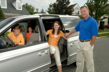 family standing around minivan