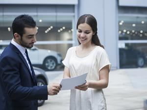Woman looking at car dealer documents