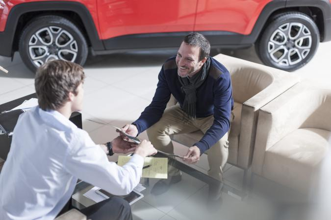 Man and car broker discussing options