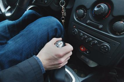 Hand on car's manual stick shift