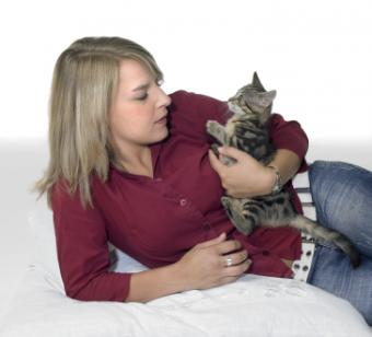 Young woman playing with her kitten