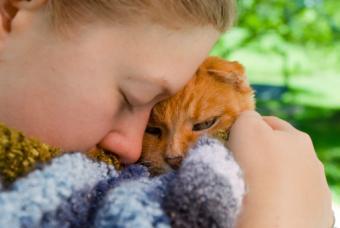 girl holding cat close