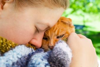 A girl holds her cat close before she has to be put to sleep