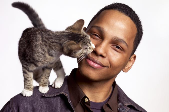 CatYoung man with cat on shoulder that it's licking his face