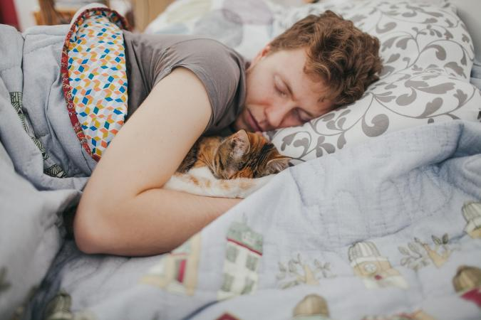 Man and cat asleep in bed