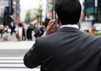 Businessman using phone on busy street
