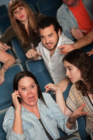 Woman talking on cellphone at the movies; © Scott Griessel   Dreamstime.com