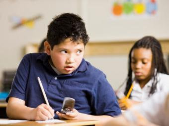 Boy cheating with cell phone