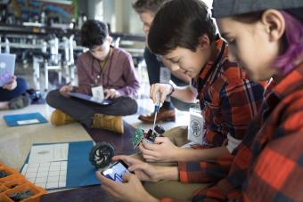 Boys assembling robotics in classroom using cell phones