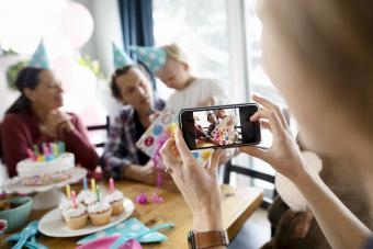 Woman with camera phone photographing toddler daughter opening birthday gift