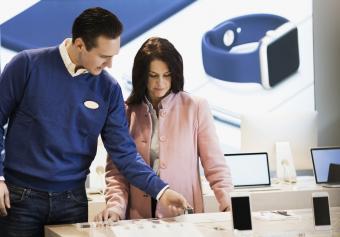 Salesman assisting customer at cell phone store