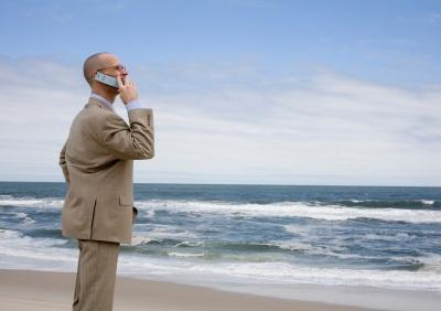 Businessman using phone on beach