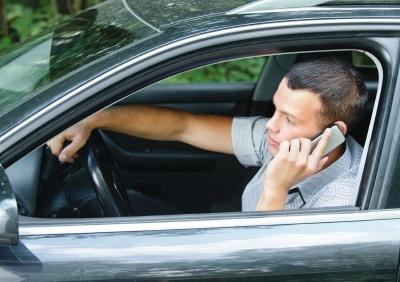 Young man speaking on phone while driving