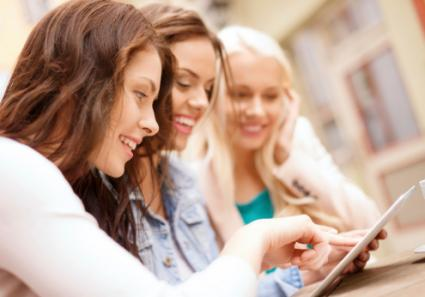 Three girls looking at tablet