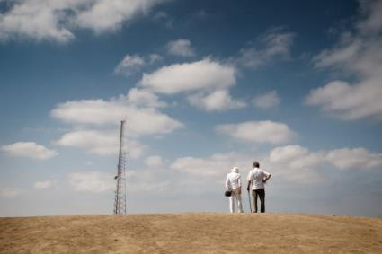 Couple looking at cell phone tower