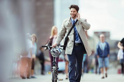 Businessman with bike talking on cell phone