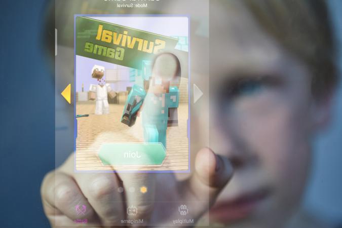boy touching Minecraft screen