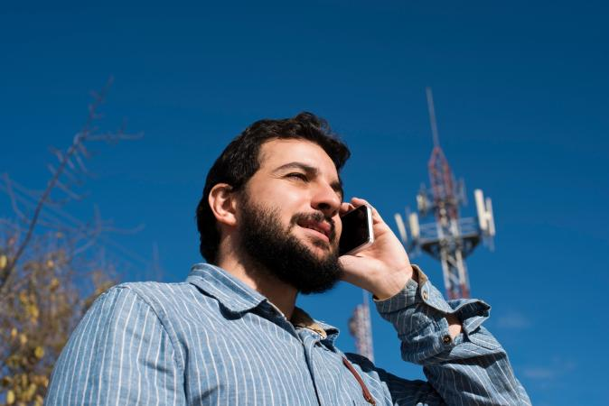 Man On Cellphone and Communication Tower