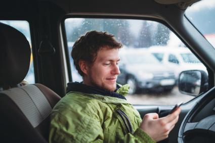Young smiling man in the green jacket holding smartphone in the car