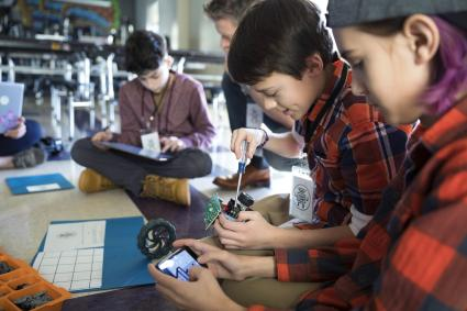 Boys assembling robotics in classroom using cell phones