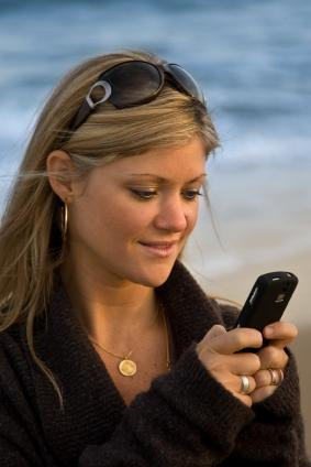 Texting from a cell phone on the beach
