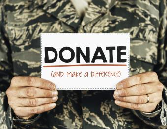 Military service member with donate sign