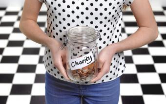 Girl holding a donation jar with coins