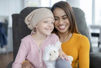 A young girl with cancer sits on her mother's lap