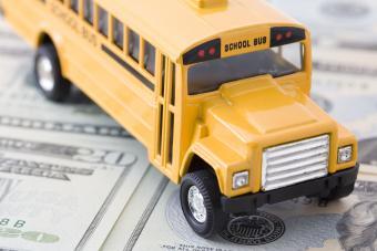 School bus toy on top of money