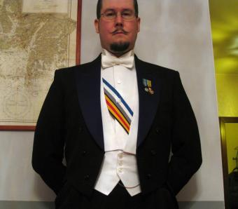 Man dressed in white tie tuxedo with decorations