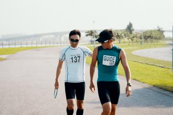 Blind triathlete and guide walking on track