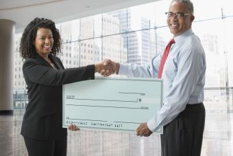 Business woman and man holding over-sized blank check