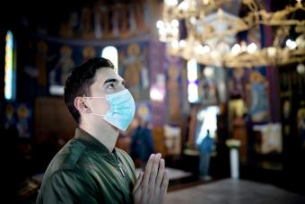 Young man wearing protective mask in church