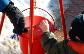 Boy donates coins during holiday season