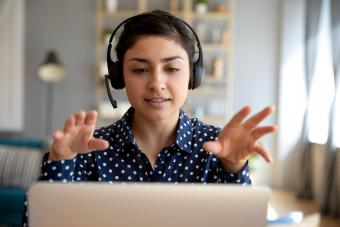 Woman wear wireless headset video calling on laptop