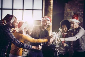 Joyful team having fun while opening champagne during Christmas celebration