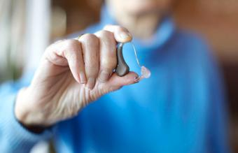 woman holding hearing aid