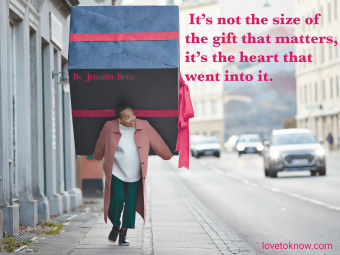 Woman carrying large gift box and quote about giving