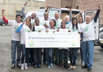 Volunteers holding community outreach banner near delivery van