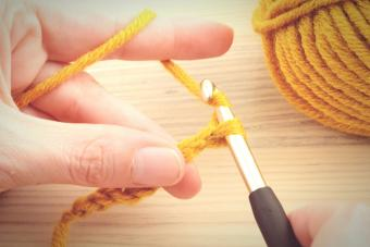 Hands Crocheting Wool Over Table