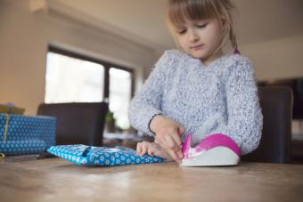 Child using adhesive tape to secure blue wrapping paper around a gift